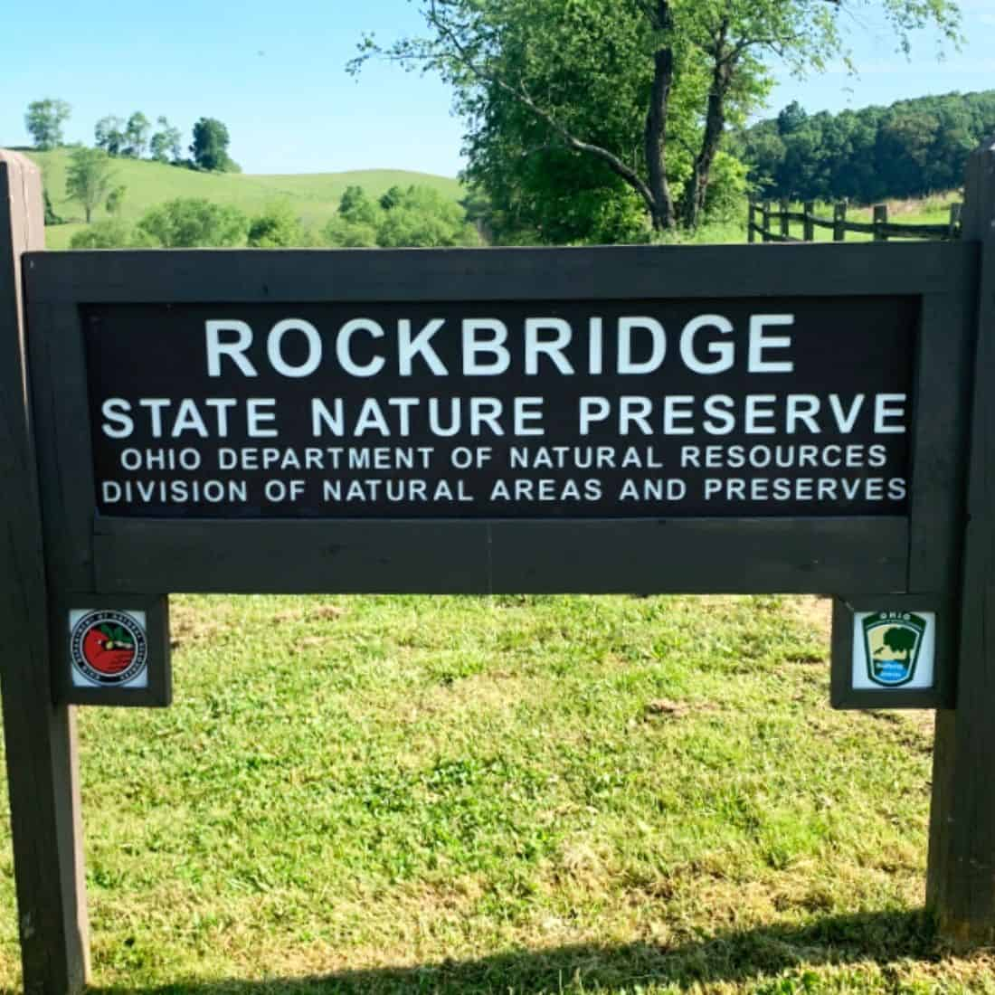Brown wooden sign with white text at the entrance to a forest that says Rockbridge State Nature Preserve