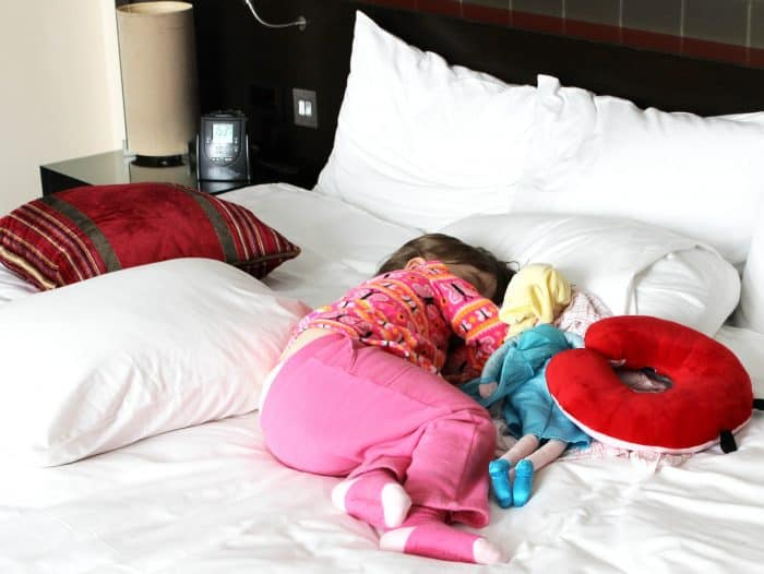 Stay healthy while traveling - Little girl taking a nap on a bed surrounded by pillows