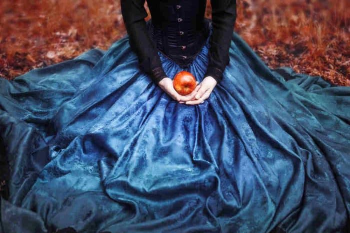 Woman in a long flowing blue dress, although you can't see her head in the picture, holding a red apple in her hand.