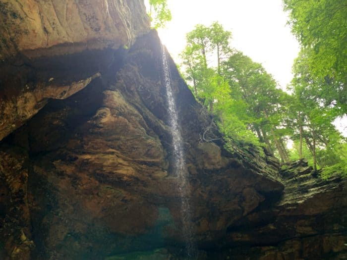 Waterfall coming over a large rock structure with a few green trees at the top and sunlight coming in