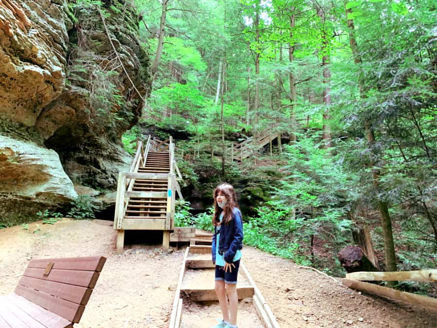 Girl walking up a wooden tiered staircase in the forest with large rocks on the left and tall green trees on the right and in front of the steps
