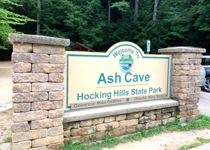 Sign saying welcome to Ash Cave Hocking Hills State Park between posts made of stone with green trees in the background