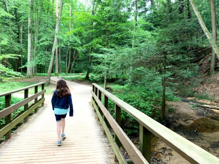 Young girl walking across a wooden bridge towards a forest with tall green trees and a paved trail