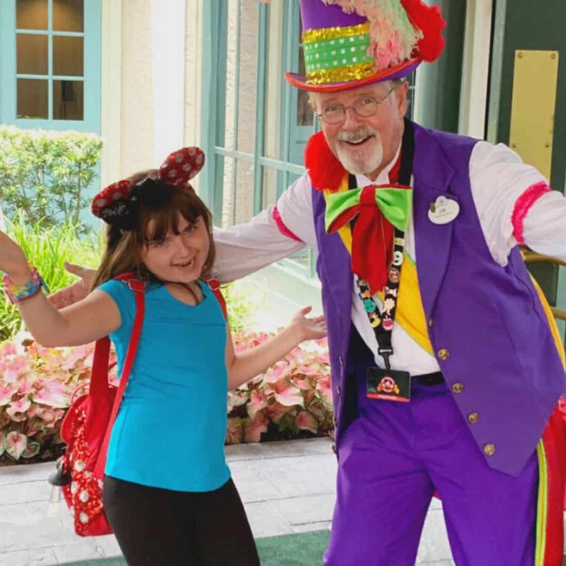 Girl in blue shirt and black pants posing with a man in a purple jester outfit