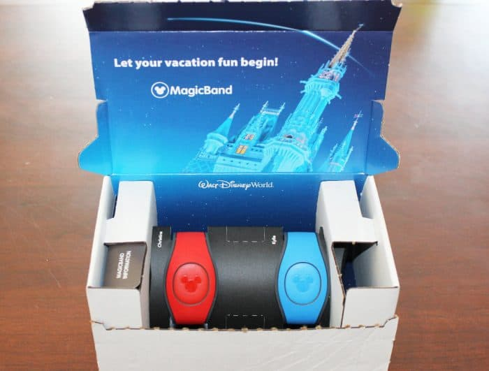 An open white box on a brown table holding a red and blue Disney Magic Band with a mickey mouse head embossed in the middle