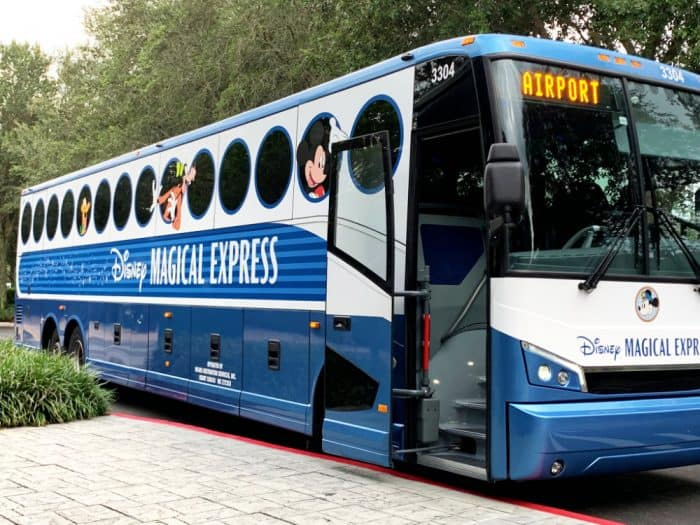 Large blue and white bus with round circle windows; Sign reads Disney Magical Express