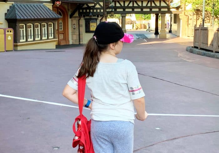Girl in gray shirt and shorts with a red bag holding onto a white rope in the middle of an empty amusement park