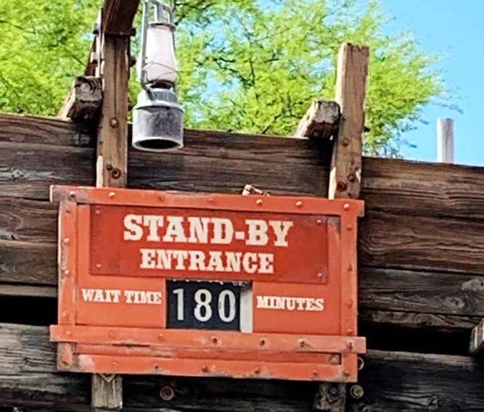Orange sign reading Stand-by Entrance wait time 180 minutes on top of wooden boards with a blue sky in background