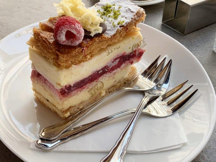 Raspberry custard tarte with three silver forks on a white plate