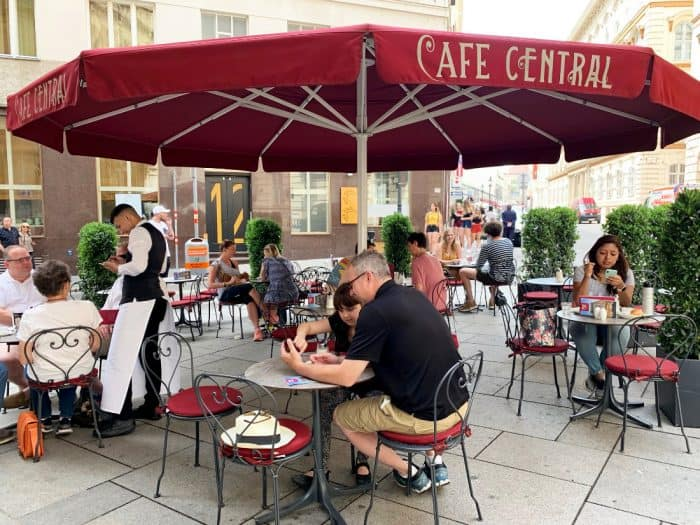 People enjoying an outside cafe sitting on wrought iron chairs with tables- Large red umbrella hangs over the tables bearing the name Cafe Central