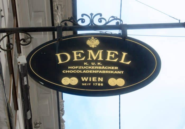 Iron sign with gold lettering 'Cafe Demel' hanging off a white facade building