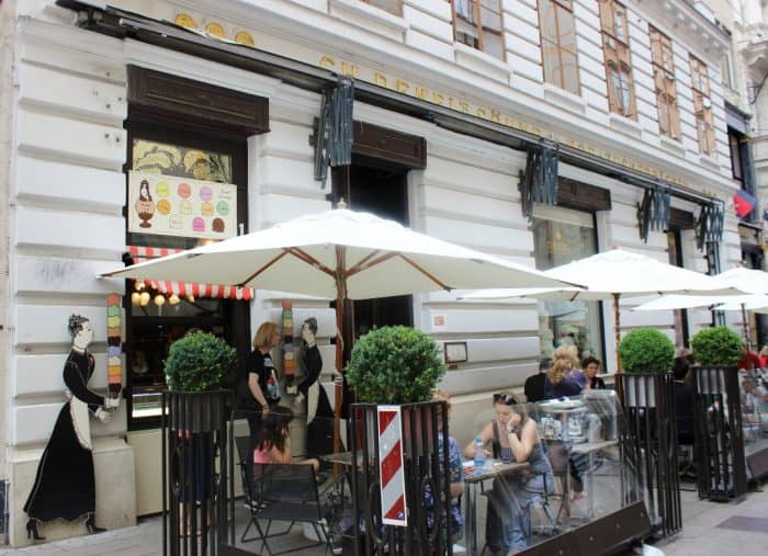 Wrought iron tables and chairs each having a white umbrella over it outside a cafe with a white facade in Vienna