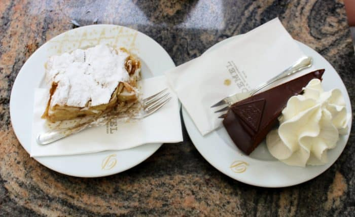 Apple strudel on a white china plate with a fork and a slice of chocolate cake and whipped cream on the side on a white china plate with a fork - on a table.