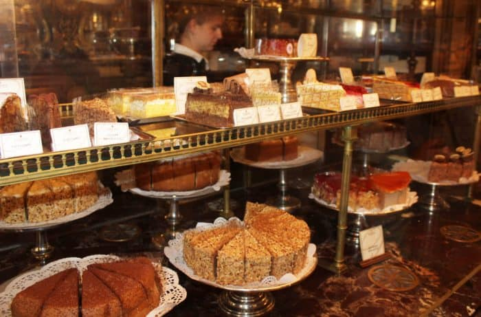 Selection of pastries arranged in 4 rows in a glass case at a cafe in Vienna