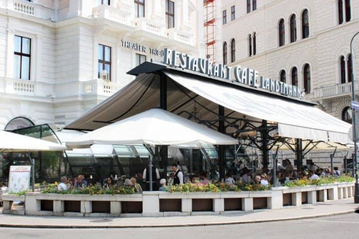 Outside cafe patio with many people sitting at tables under a large white canopy with the words 'Landtmann' on it
