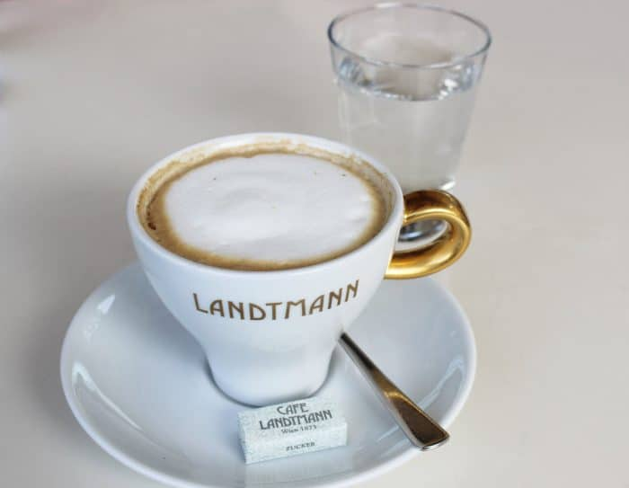 Melange coffee in a white china cup with gold handle and golden words 'Landtmann' on cup, sugar cube, spoon and glass of water on a table