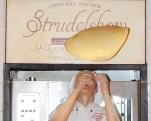 Woman in bakers hat and coat flipping a piece of dough over her head in front of a large baking oven