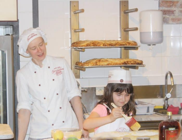 Baker and little girl basting a strudel with butter