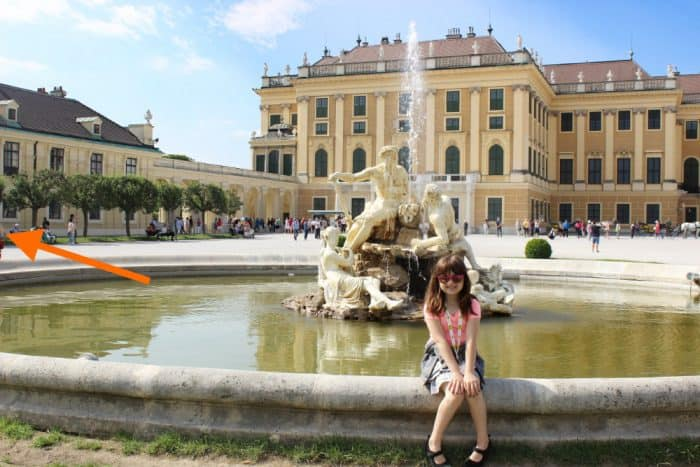 Girl sitting on edge of a fountain in front of a yellow and gold palace