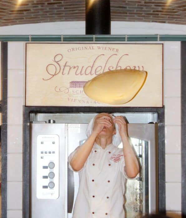 Baker twirling the strudel dough above her head while making the best apple strudel in Vienna
