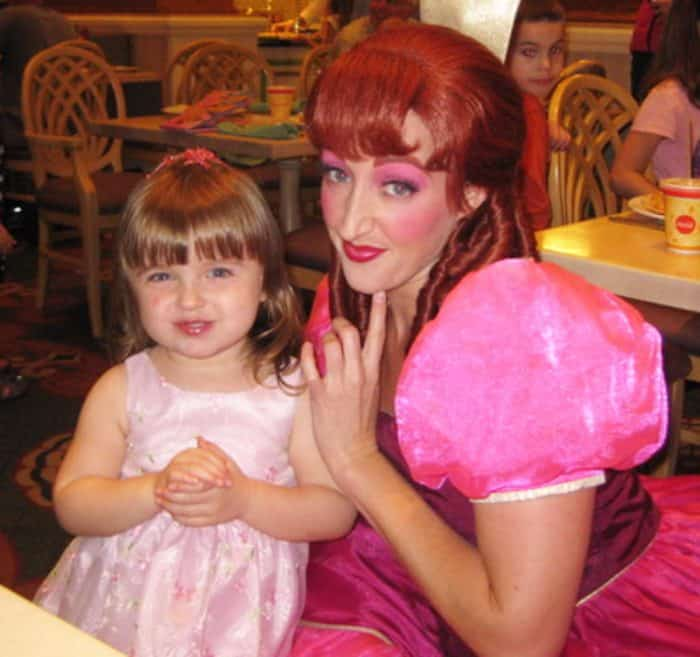 Little girl in pink dress posing with Disney's Anatasia at a character meal at Disney