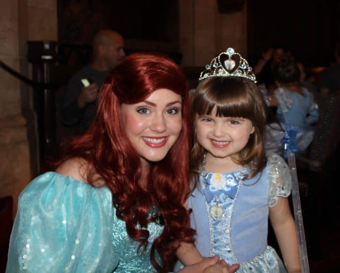 Little girl in blue princess dress with tiara posing with Disney's Princess Ariel who has long red hair and a turquoise dress.