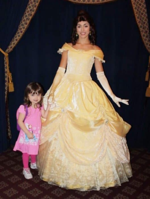 Little girl in pink dress posing with Disney's Princess Belle who is dressed in a long, yellow ball gown.