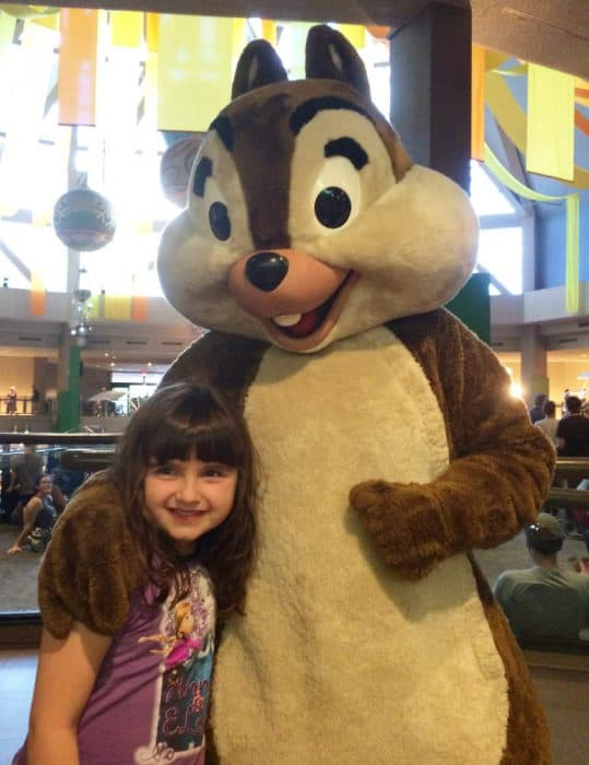 Young girl in purple tshirt and brown hair hugging Chip, a Disney fur character that is a chipmunk.