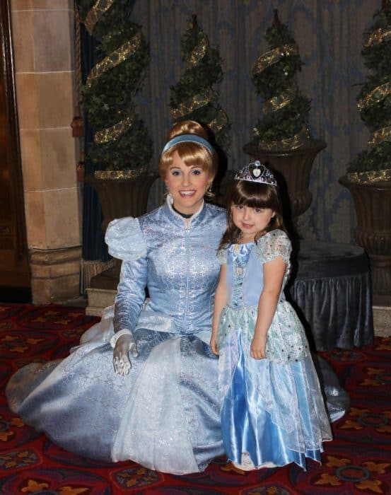 LIttle girl in blue princess dress and tiara posing with Disney's Cinderella also dressed in long, blue ball gown.