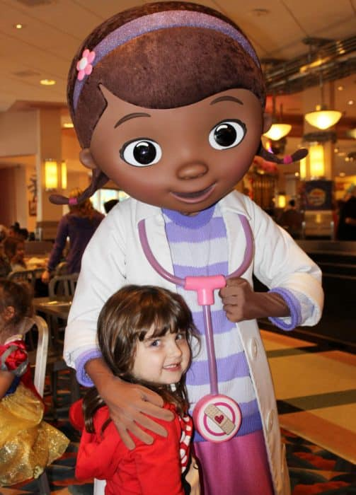Little girl in red shirt hugging Disney's Doc McStuffins