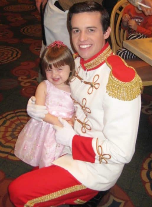 Little girl in pink dress hugging Disney's Prince Charming - man wearing white coat and red pants
