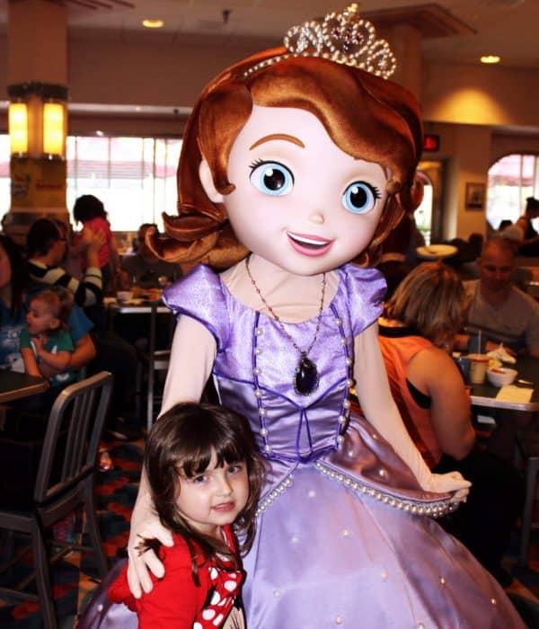 Little girl in red shirt hugging Disney's Princess Sophia.