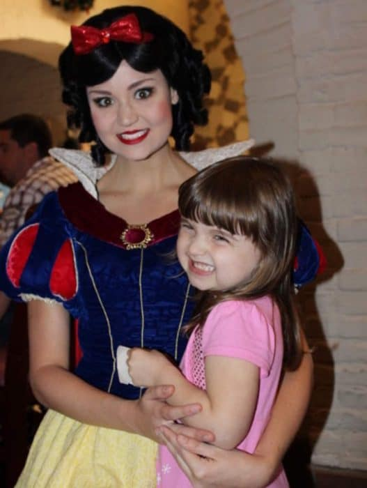 Little girl in pink dress hugging Disney's Snow White in a blue and yellow dress.