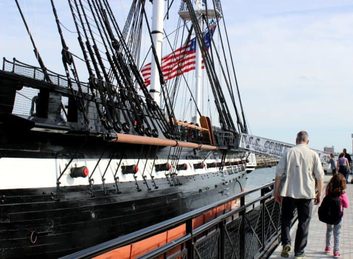Man in beige shirt and little girl with black backpack walking next to a large black and white ship with tall masts with the signage USS Constitution