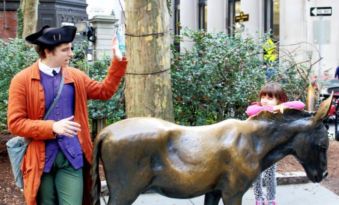 Man dressed in 1800's attire with purple vest, orange sweater and a black hat next to a bronze horse statue with a little girl resting on the statues' neck