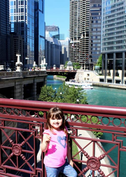 Little girl in pink short sleeve top standing next to a brown gated railing over a river with a ferry boat and tall glass buildings surrounding it.
