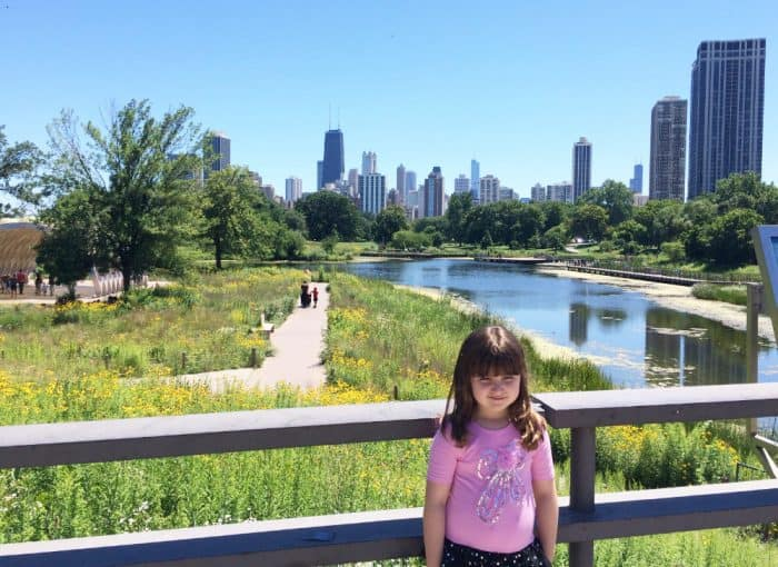 Little girl in pink shirt in front of a park with a pond with tall buildings of a city in the background