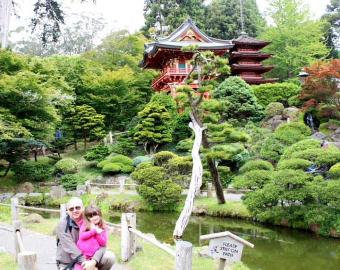 Man hugging little girl in hot pink jacket posing in front of Japanese styled trees and a red tea house