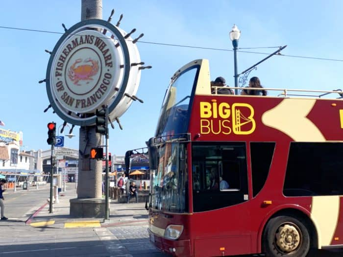 Red double decker bus in front of a large sign in the shape of a ships steering wheel that says Fishermans Wharf of San Francisco