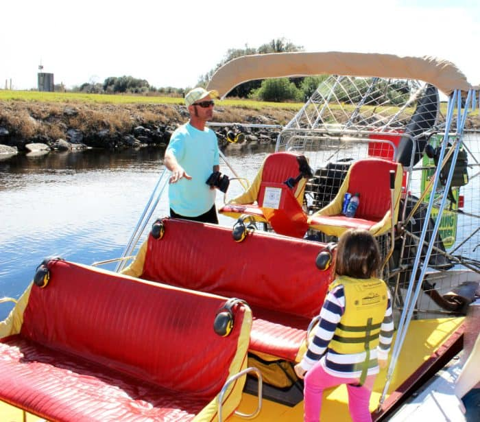 Red and yellow seats in an airboat on the water with a little girl in yellow life vest and man in aqua tshirt on the boat