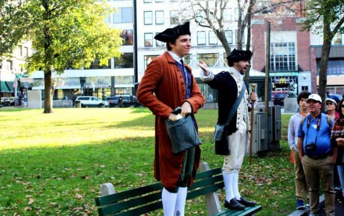 Two men dressed in colonial clothes with white stockings and black shoes standing on a park bench talking with a crowd of onlookers