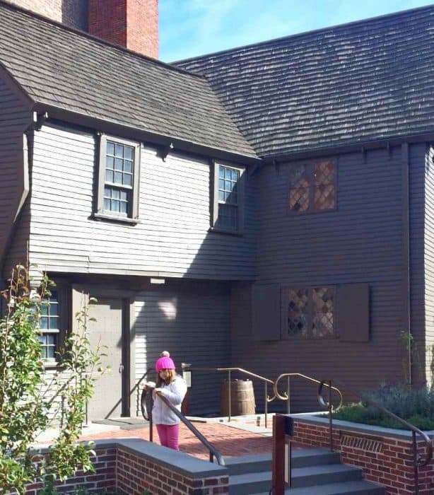 Girl in pink pants and hat with white jacket leaning on a rail in front of a brown sided two story house with orange chimney