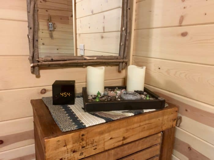 Wooden drawers with a rock and 2 candle display along with a black cube digital clock and mirror hanging on wall