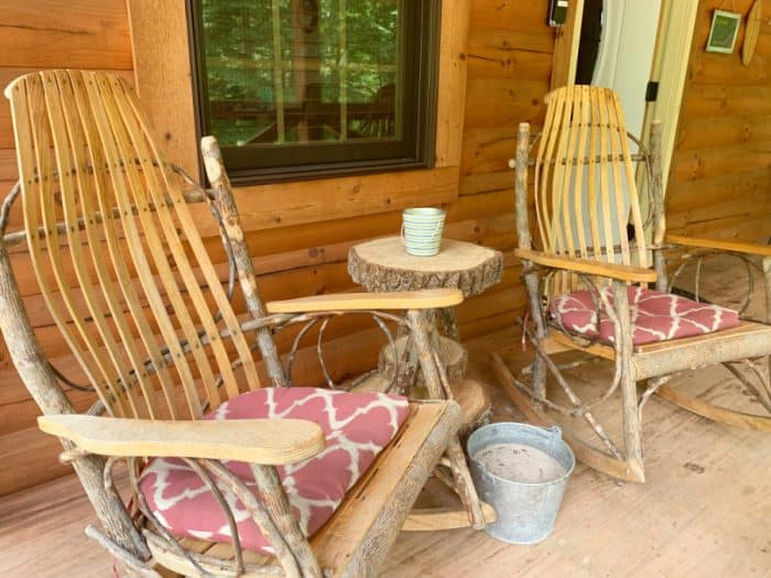 Two log and wooden rocking chairs on a porch with a log table and small candle jar on top and a pail of sand on the ground