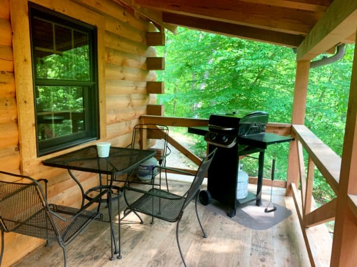 Log cabin outside porch with black grill and black wrought iron table with 3 chairs
