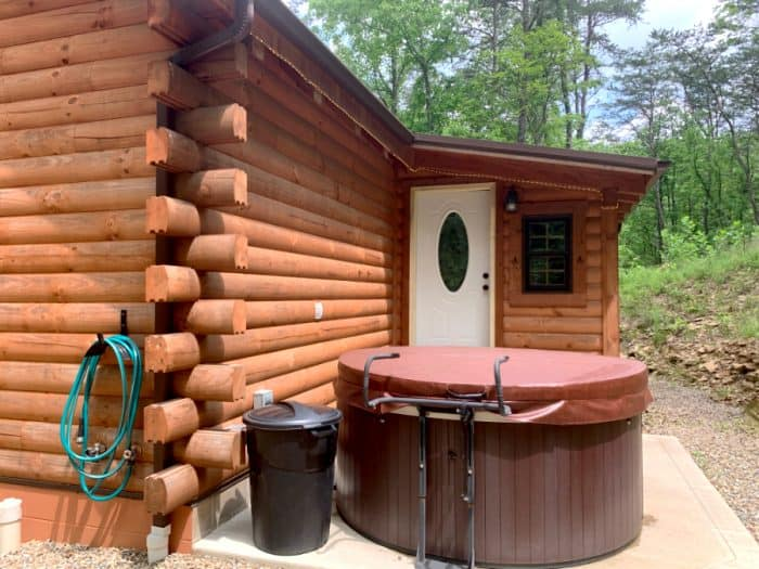 Log cabin with a green garden hose hanging on it, a black trash can, a brown covered hot tub and white door to the cabin.