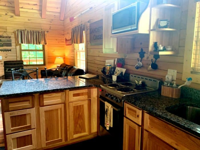 Kitchen area of a log cabin with wooden cabinets and granite countertops, a stove and coffee cups hanging on the wall