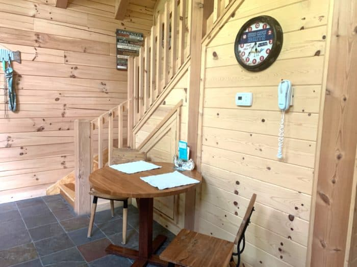 Inside a cabin with light wooden walls with a staircase going up and a small kitchen table with 2 chairs