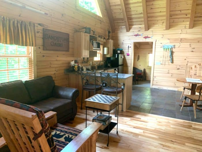 Cabin with light wooden walls, a chair, brown leather couch, kitchen and island with two bar stools and a table to the right