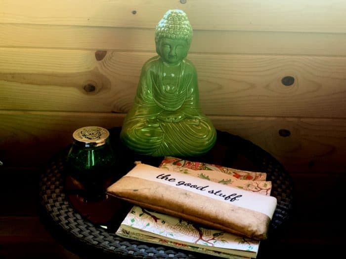 Jade buddha, a small bag labeled 'the good stuff' and coloring books on top of a table